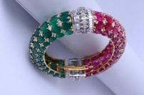 DIAMOND BRACELET IN 14 KARAT YELLOW GOLD COMPLIMENTED WITH A COMBINATION OF OVAL SHAPED RUBIES AND GREEN ONYX